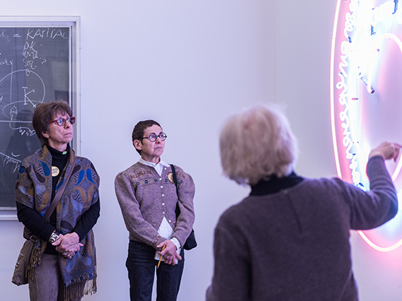 A guide gives a tour of the collection to visitors.