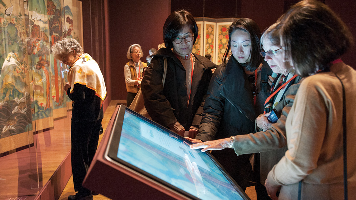 Group of visitors using an interactive touch screen in the galleries