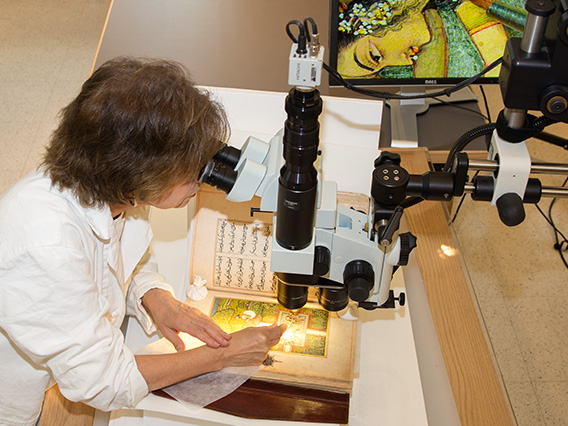 Conservator looking at an artwork through a microscope