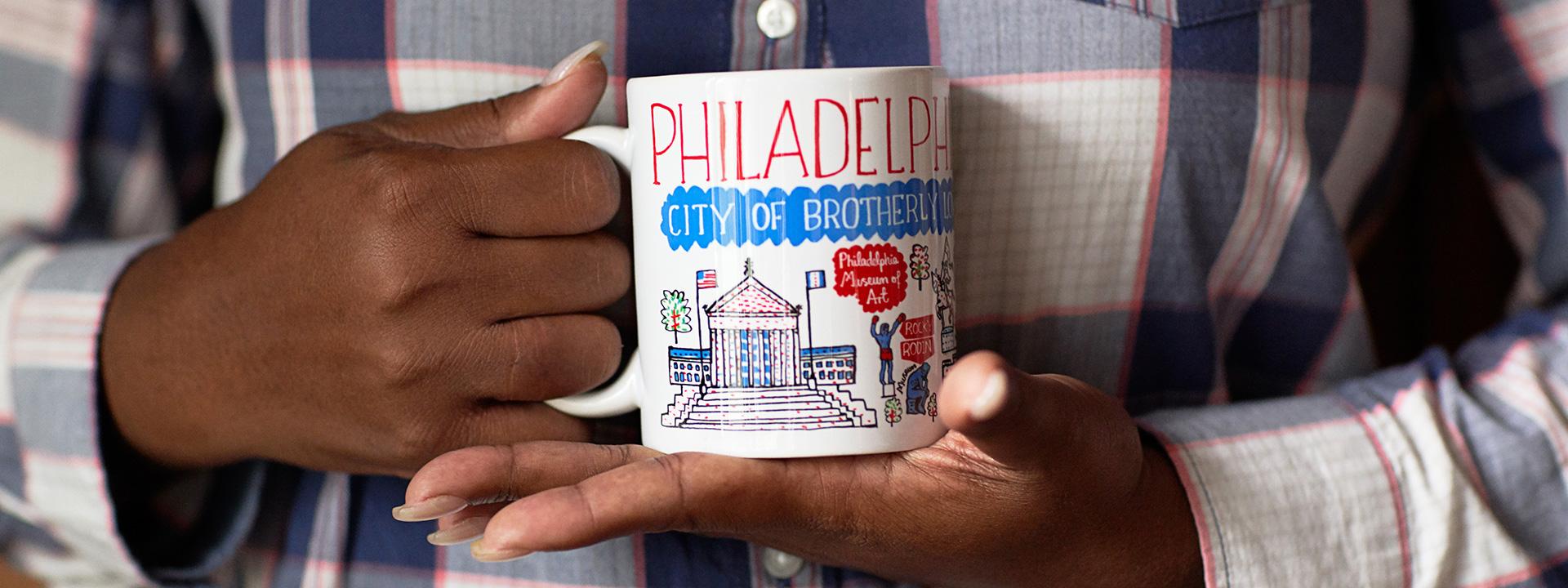 Person holding a Philadelphia coffee mug