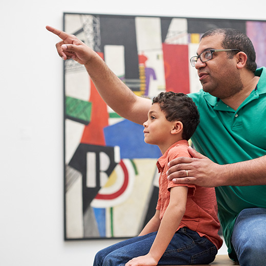 A parent showing his child an artwork