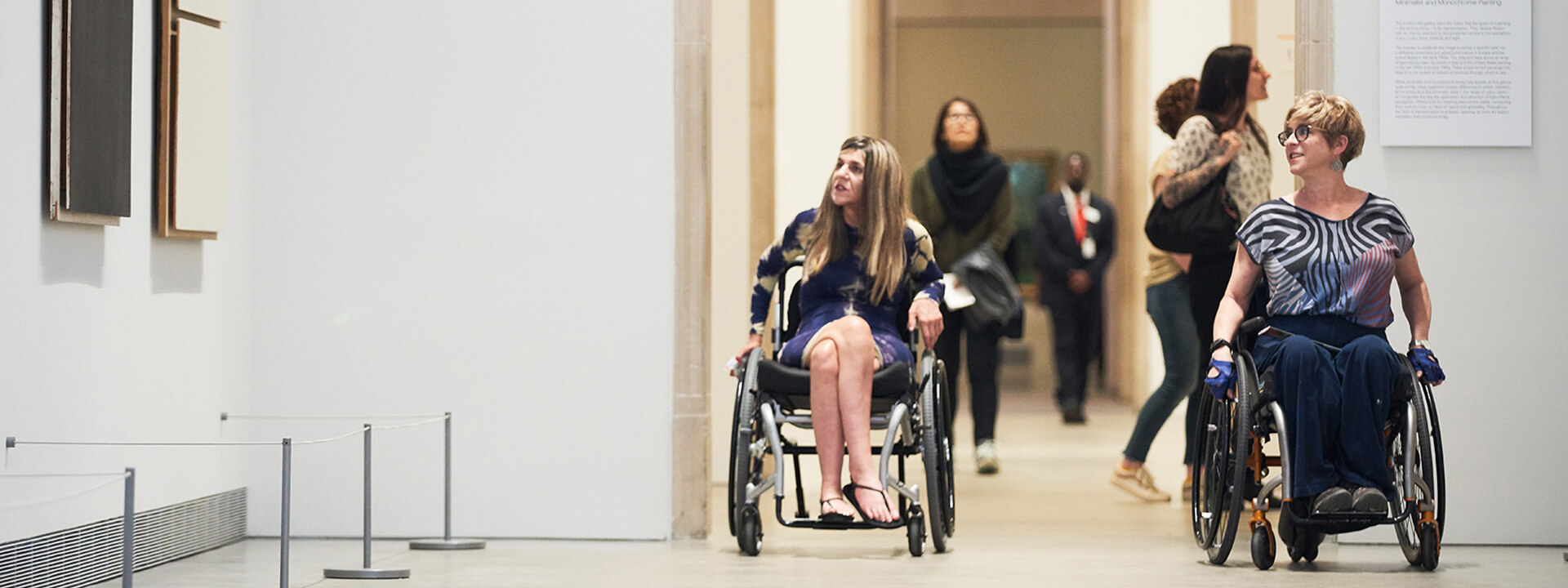 Two visitors in wheelchairs explore the galleries