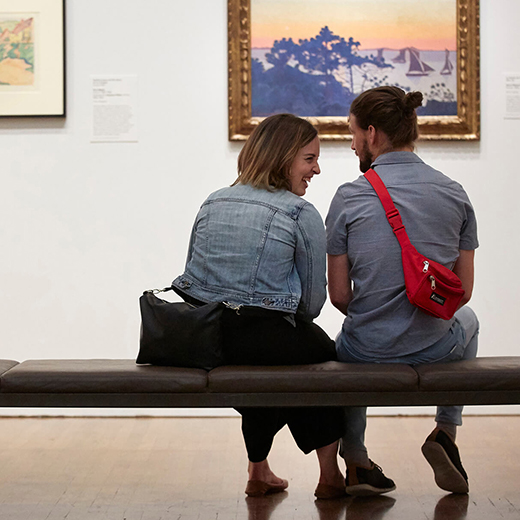 A young couple chat while seated on a bench in a gallery