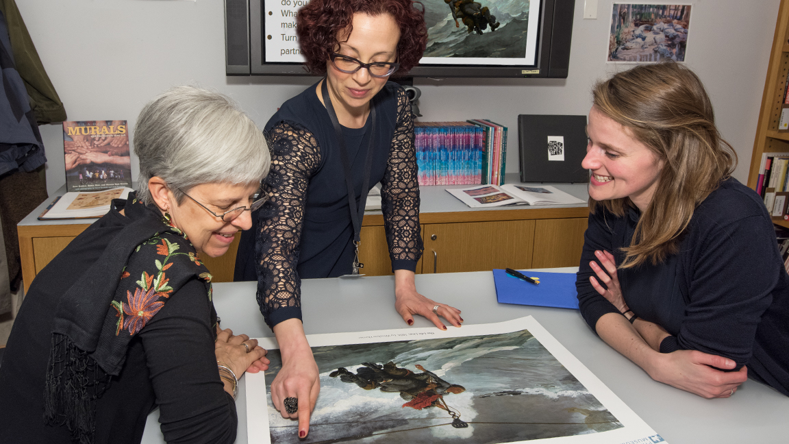Three teachers reviewing a teaching poster together in the Wachovia Education Resource Center