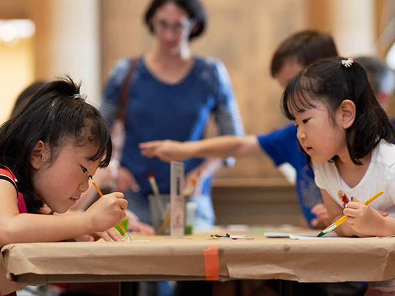 Two young girls making art together at a table