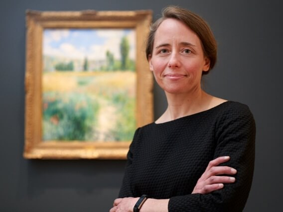 Curator Jenny Thompson standing with arms folded in front of an Impressionist painting