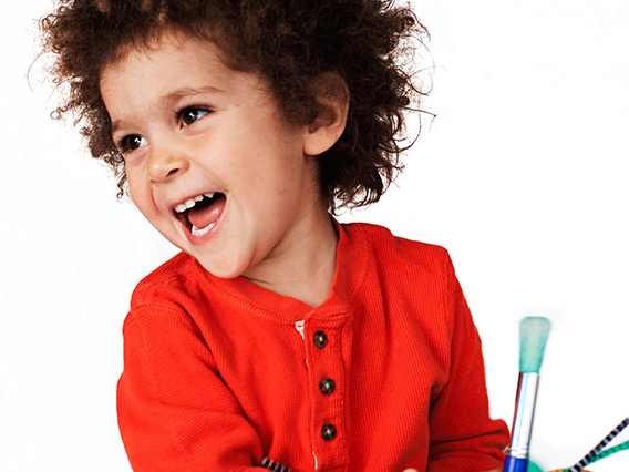 Young child smiling while holding a paintbrush