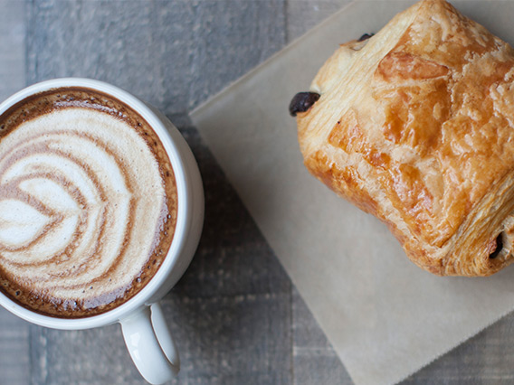 Cup of foamy espresso next to a chocolate croissant