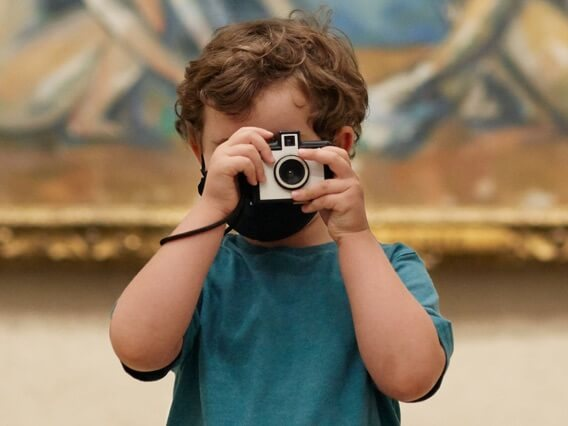 Young child holding a toy camera their face in front of a large painting
