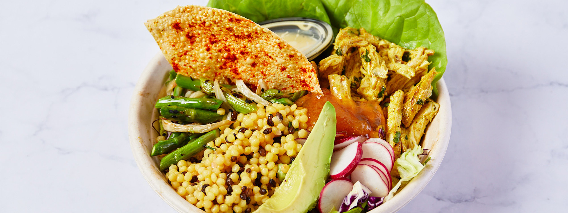 Grain bowl with chicken, avocado, radishes, and assorted vegetables