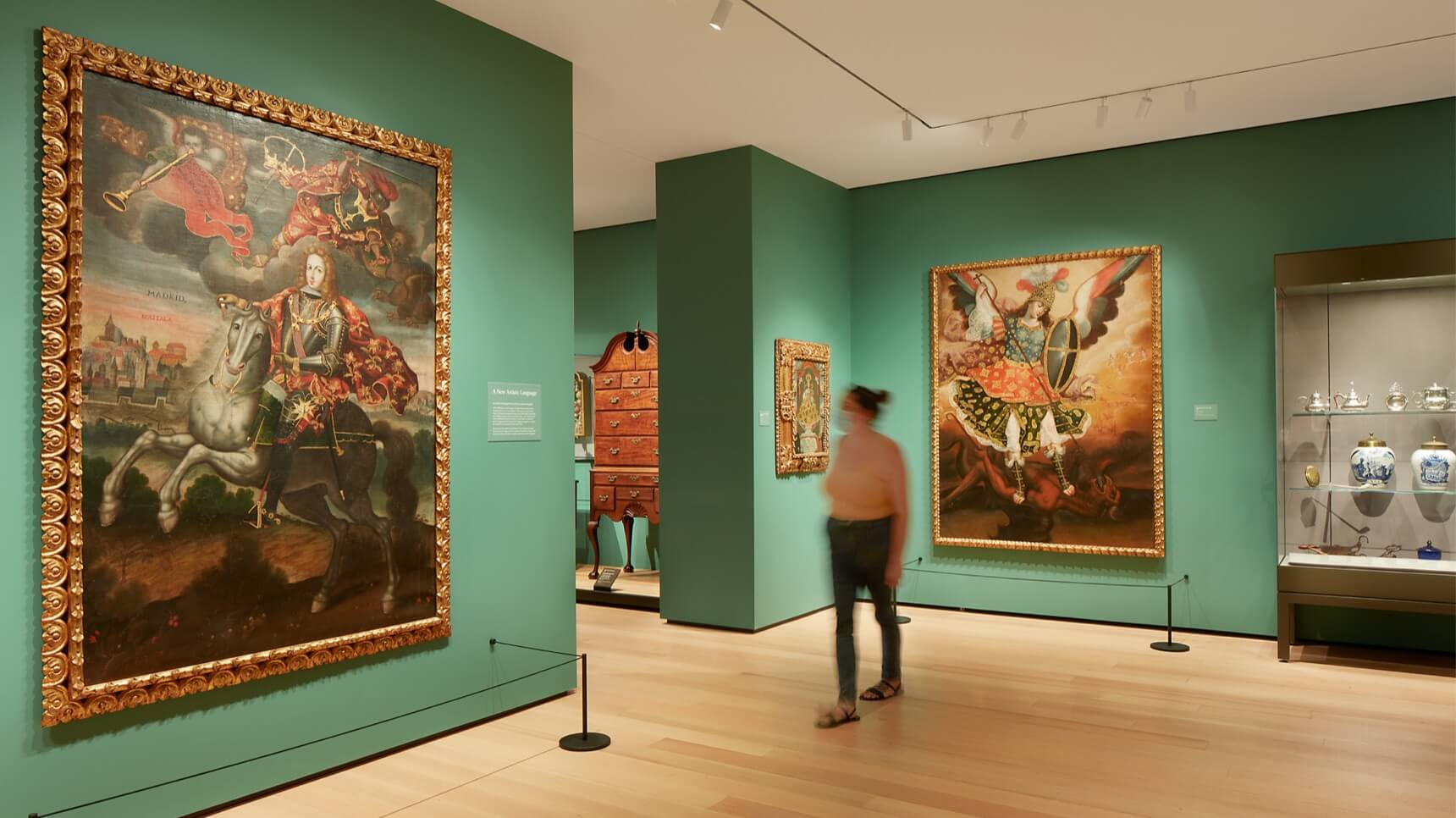 Masked visitor walking through galleries with green walls and large colonial Latin American paintings