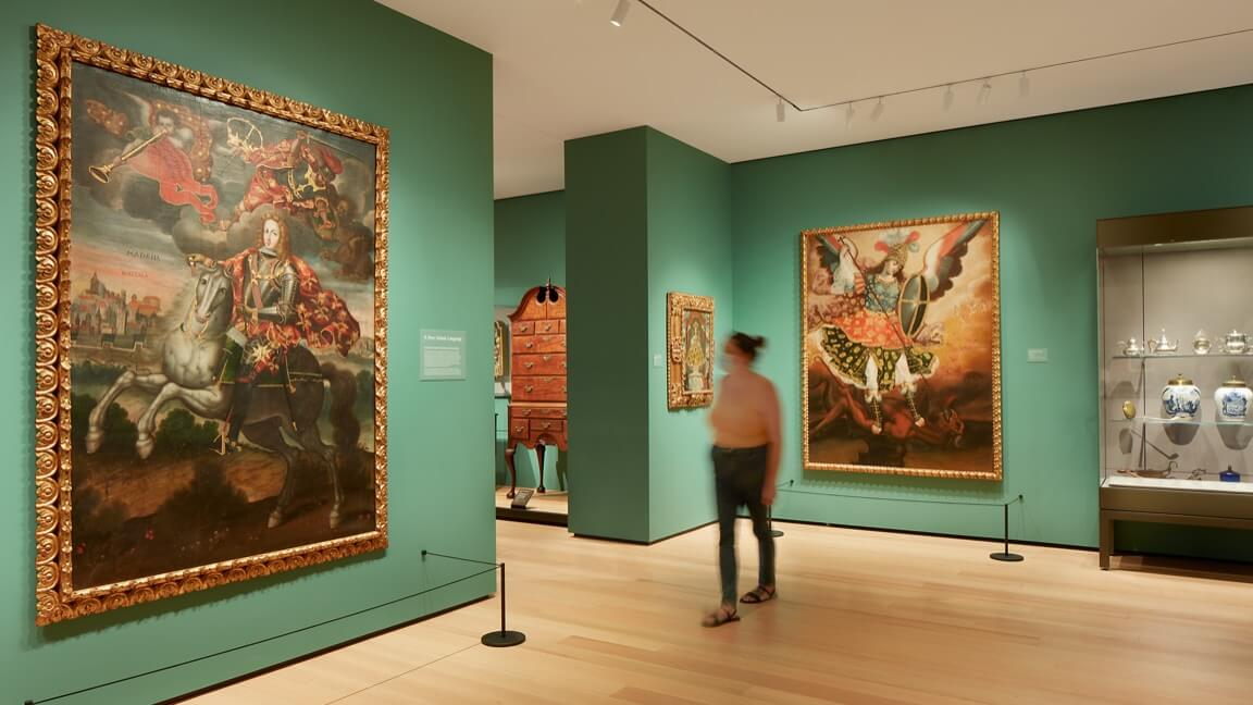 A masked visitor in a gallery with green walls and large paintings
